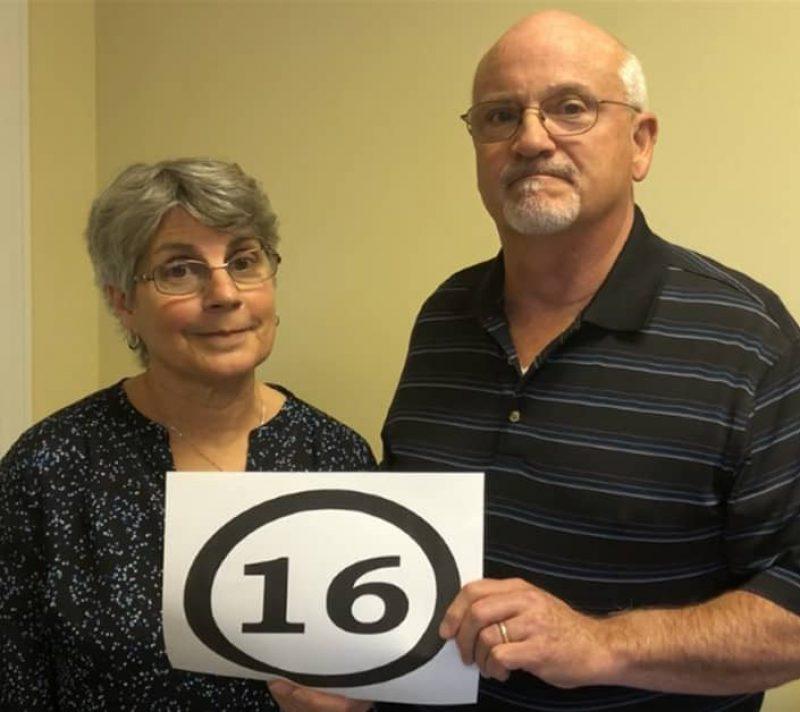 man-women-holding-16-sign