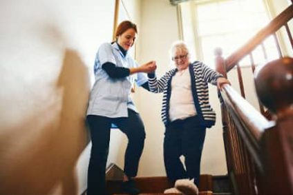 women-helping-senior-walk-down-stairs