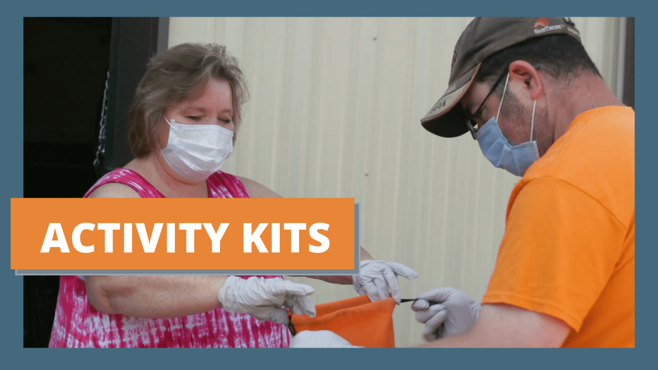 """a white woman with short hair and a mask and gloves on holds upon a bag as a white man with a mask and gloves on places items in the bag. Text reads """"Activity Kit"""""""