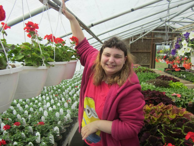 A young woman with sandy blonde hair smiles at the camera while reaching up to grab a hanging planter full of geraniums in a greenhouse