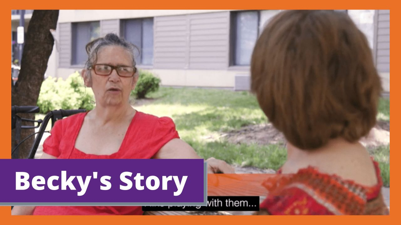 """An older white woman sits on a park bench and talks to another white woman sitting on the other side. Text reads """"Becky's Story"""""""