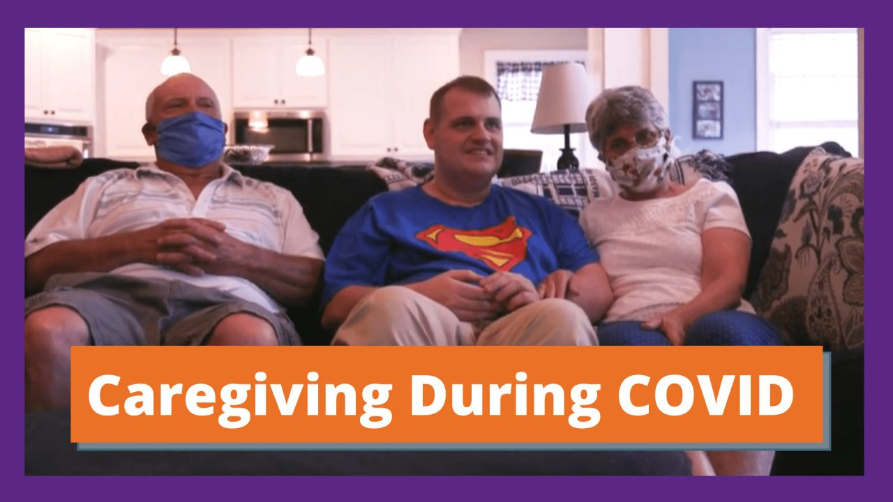 """An older white couple with masks on sit on a couch with their son sitting in between them. The young man smiles at the camera and wears a superman shirt. Text reads """"Caregiving During COVID"""""""