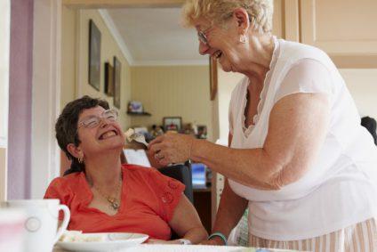 caretaker helping woman eat