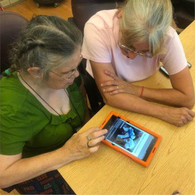 women-helping-women-on-tablet