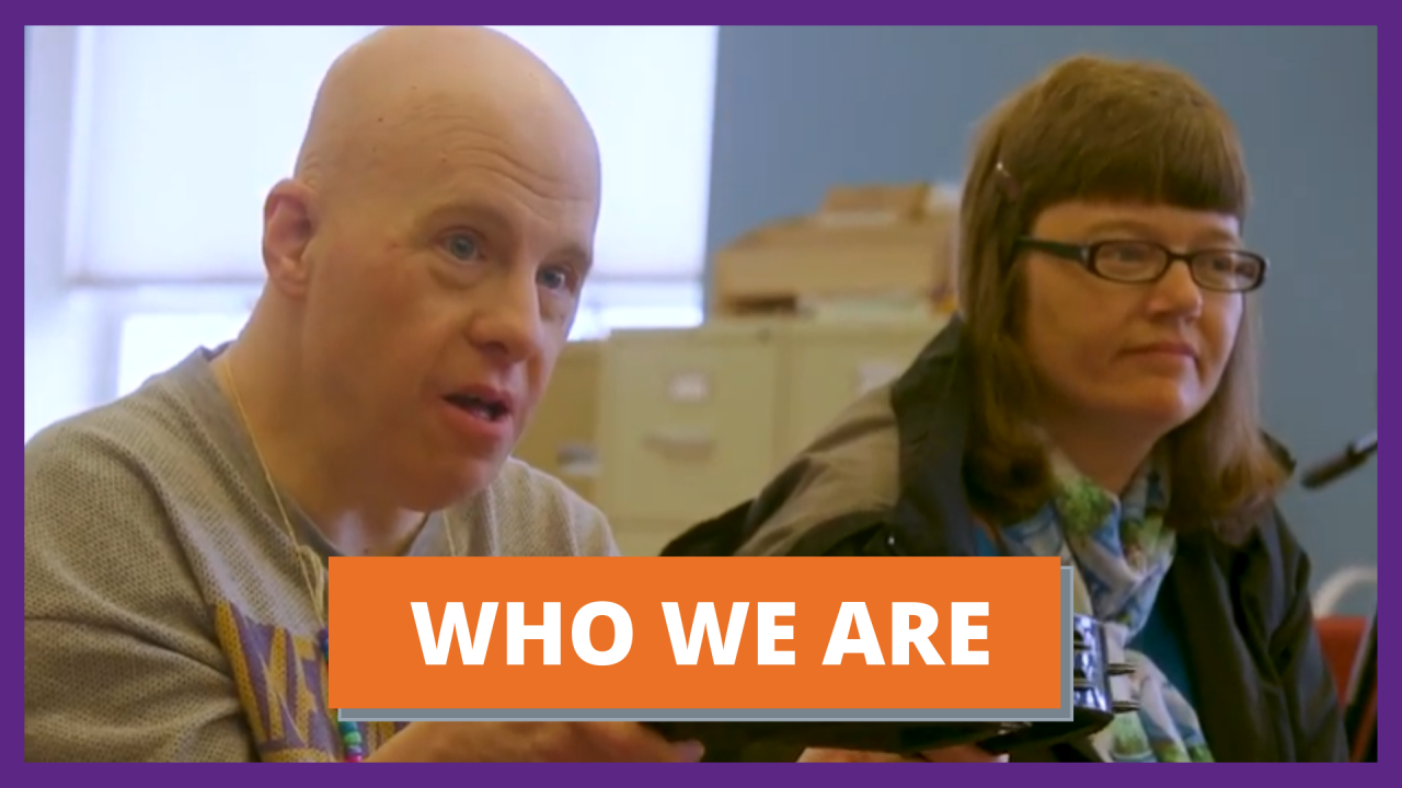 """A close up of an older white, bald man who holds a tambourine and sits next to a white woman with brown hair and glasses. They are both looking at someone off camera. Text reads """"Who We Are"""""""